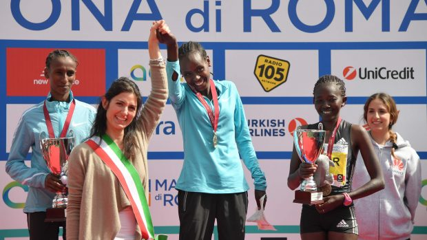 Rahma Tusa (C) from Ethiopia, winner, Dalila Abdulkadir Gosa (L), second, and Kenya's Alice Jepkemboi Kibor (R), third, pose on the podium with the mayor of Rome Virginia Raggi, after the 24th edition of Rome Marathon, on April 8, 2018 in Rome. / AFP PHOTO / Tiziana FABI
